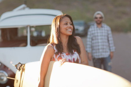 Young woman holding surfboard on road trip,smiling