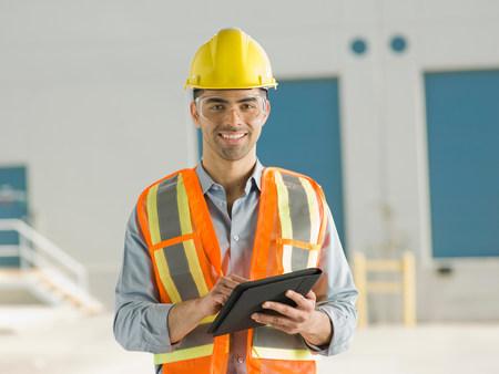 Mid adult construction worker using digital tablet,portrait LANG_EVOIMAGES