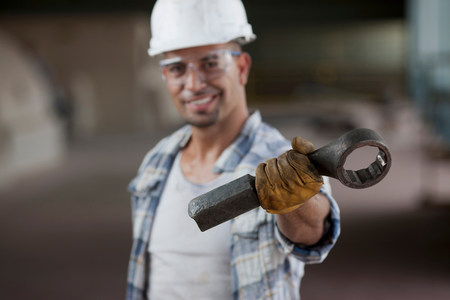 Mid adult construction worker wearing hard hat and holding wrench,portrait LANG_EVOIMAGES