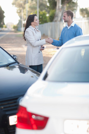 Drivers of car accident shaking hands