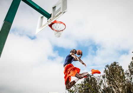 Young man jumping to score hoop in basketball