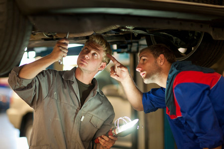 Car mechanics discussing and analyzing car repair