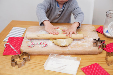 exerting: Boy rolling cookie dough,baking Christmas biscuits