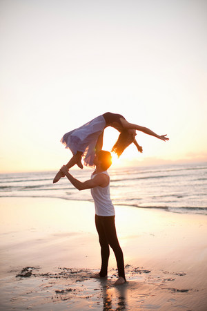 arms lifted up: Young man lifting dancing partner on sunlit beach