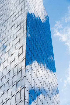 tallness: Blue cloudy sky reflected in windows of modern skyscraper