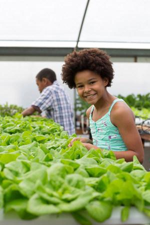 afro caribbean ethnicity: Children tending plants in nursery