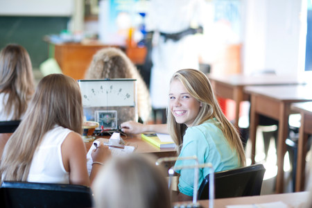 schoolroom: Girl turning around to look at her classmates