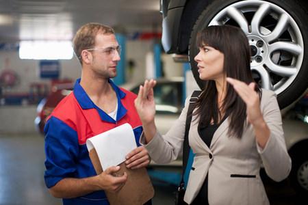 Car mechanic and customer discussing car repair LANG_EVOIMAGES