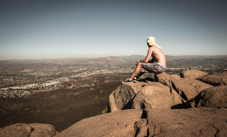 Man sitting on rock looking at view over San Diego,California,USA LANG_EVOIMAGES