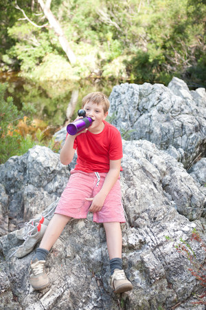 top 7: Portrait of young boy drinking from flask on rock LANG_EVOIMAGES
