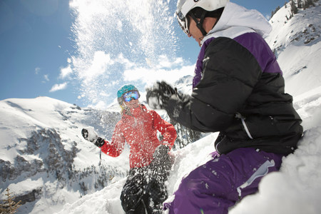 two persons only: Mid adult man and young woman in skiwear having snowball fight LANG_EVOIMAGES
