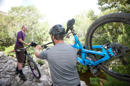 Young couple with mountain bikes on rock