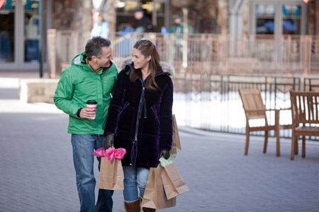 Young woman carrying shopping bags with mature man