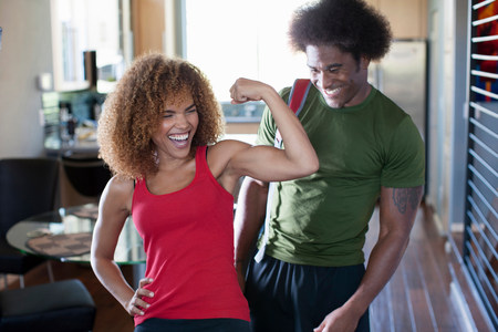 build in: Mid adult woman flexing bicep in front of mature man,smiling