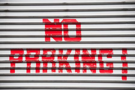 enforcing: Red hand painted no parking sign LANG_EVOIMAGES