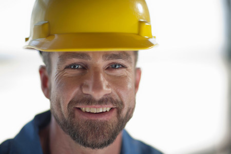 protects: Mid adult construction worker wearing hard hat,smiling
