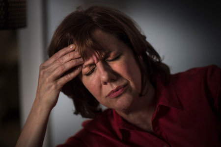 inconvenient: Mature woman with hand on head and eyes closed
