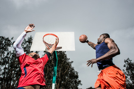 Young basketball players jumping to score hoop LANG_EVOIMAGES