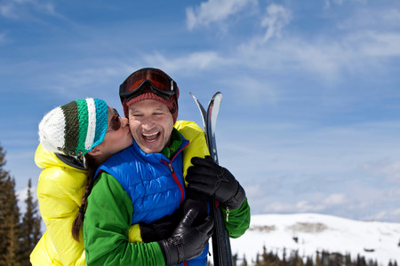 smooching: Young woman in skiwear kissing mature man holding skis LANG_EVOIMAGES