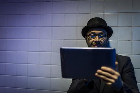 Portrait of man using digital tablet underground LANG_EVOIMAGES
