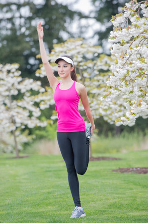 Teenage girl wearing pink sportswear stretching in park
