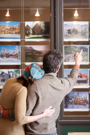 45 50: Couple looking at photographs in travel agents window,rear view