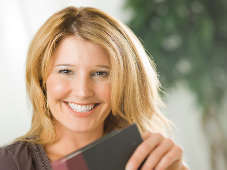 tomes: Mid adult woman holding notebook and smiling