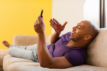 purples: Mid adult male on sofa using digital tablet LANG_EVOIMAGES