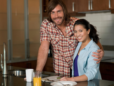 worktops: Young woman and mid adult man smiling in kitchen,portrait