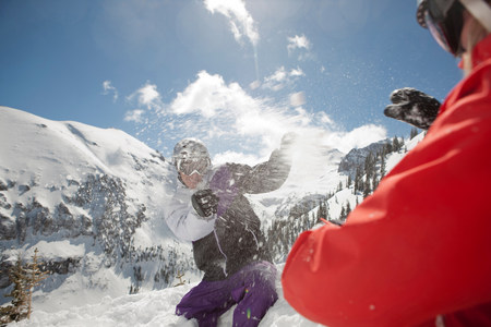 wintry weather: Mid adult man and young woman in skiwear having snowball fight LANG_EVOIMAGES