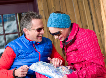 Mature man and young woman looking at map in ski resort