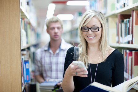 Female student using smartphone in library,man in background LANG_EVOIMAGES