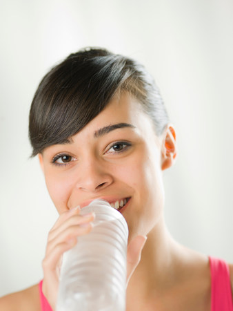 Young woman drinking from water bottle