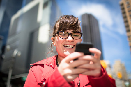 state of mood: Portrait of woman in city looking at smartphone