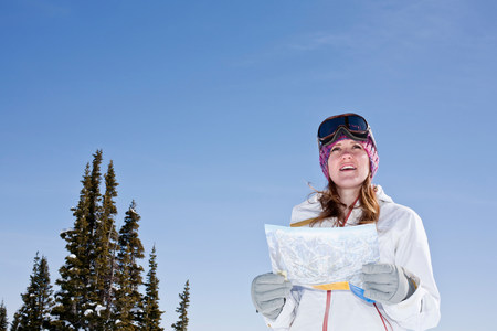 Young woman holding ski map
