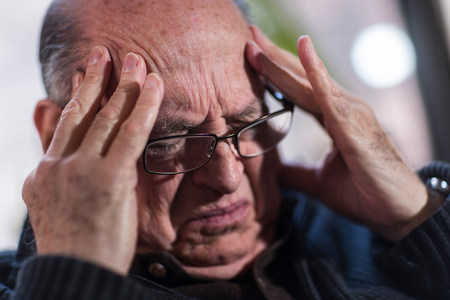 70 75: Senior man with eyes closed,wearing glasses,looking stressed
