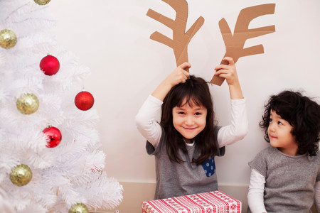 two persons only: Two girls preparing for Christmas,playing with cardboard reindeer antlers