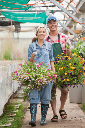 Young woman and mature man walking with hanging baskets in garden centre LANG_EVOIMAGES