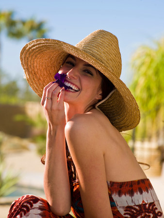 Young woman wearing sun hat and holding purple flower petal,portrait
