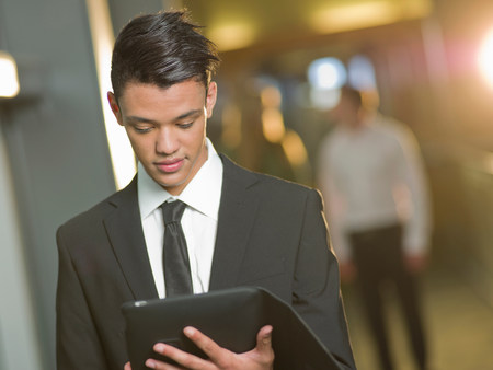 business: Young businessman in black suit using digital tablet