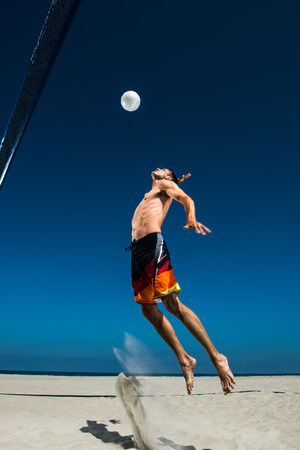 40 years: Male beach volleyball player jumping mid air to hit ball