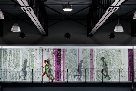 exerting: Young woman jogging on gym balcony