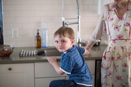 sinks: Boy at kitchen sink looking over shoulder