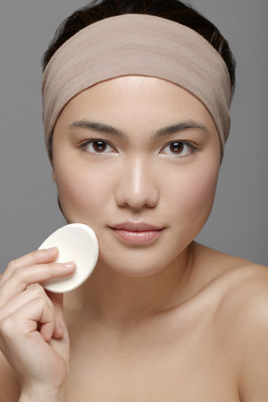 alice band: Young woman using make up sponge LANG_EVOIMAGES