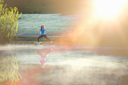 Teenage girl stretching by misty lake in sunlight LANG_EVOIMAGES