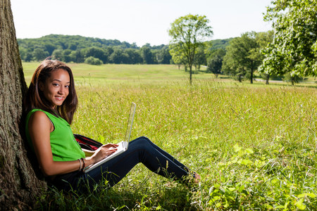 forge: Young woman using laptop sitting by tree LANG_EVOIMAGES