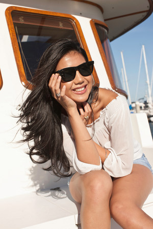 affluent: Portrait of young woman sitting on yacht,San Francisco,California,USA LANG_EVOIMAGES