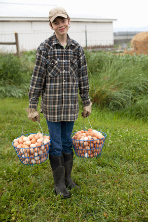 Boy carrying two baskets of eggs