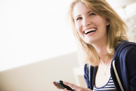 chuckle: Young woman with cell phone,laughing