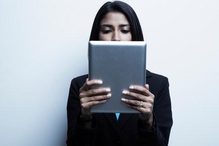 engrossed: Studio portrait of businesswoman holding digital tablet LANG_EVOIMAGES